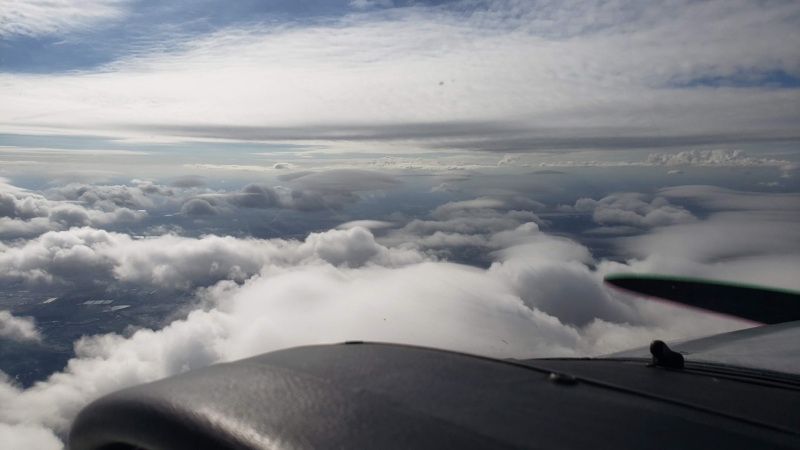 Cockpit view above a broken layer of clouds